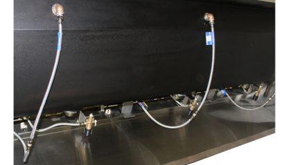 SurgiKleen stainless steel floor mounted medical scrub sink view of rear side plumbing detail